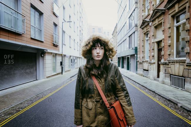 Portrait of young woman in street with bag