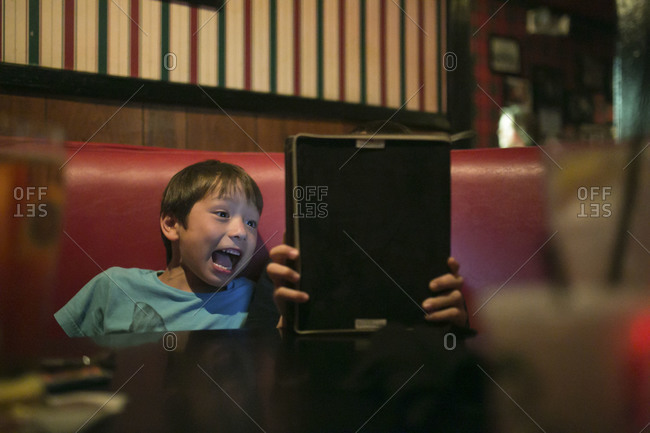 Two boys laughing at tablet in restaurant