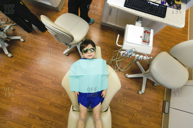 Overhead of boy in dentist\'s chair with bib