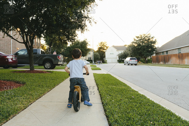 Boy riding bike down subdivision street at sunset