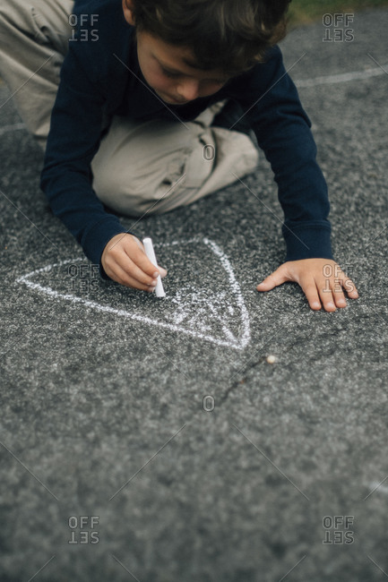 Boy drawing with chalk on concrete