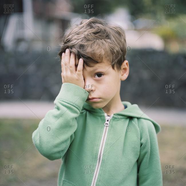 Portrait of boy rubbing eyes in hoodie