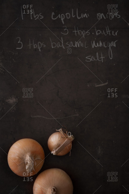 Raw onions on a chalk board with a recipe