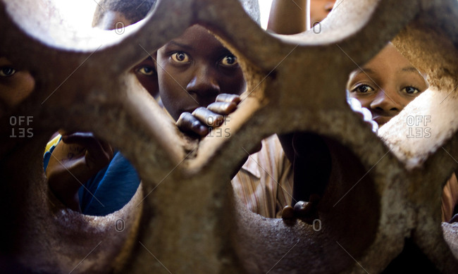 Lilongwe, Malawi - April 16, 2013:Children look through a wall Chiponde Primary school in the Rural East District
