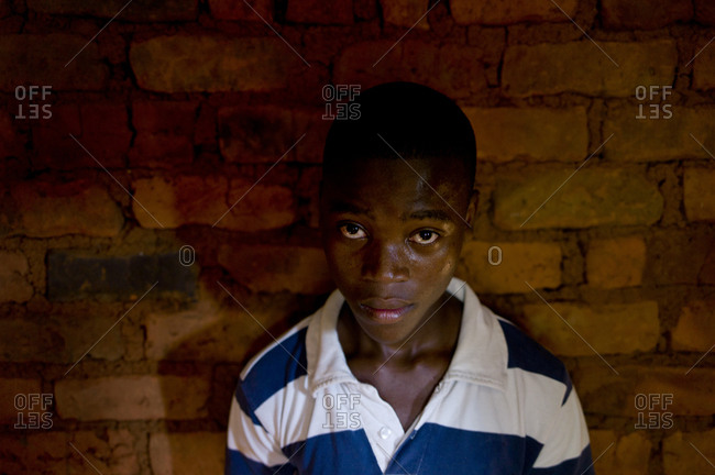 Luchenza, Malawi - April 18, 2013: A boy stands against a wall at the Komai school program