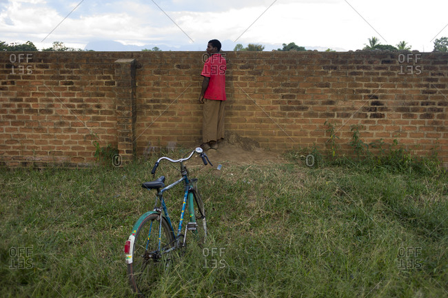 Luchenza, Malawi - April 19, 2013: A man peers over a wall