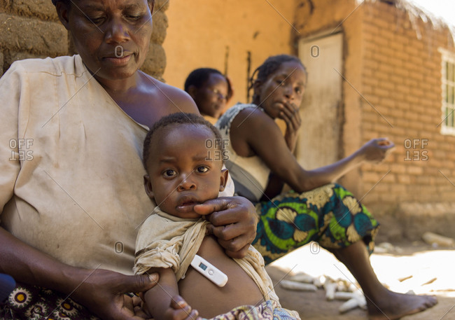 Thyolo, Malawi - April 22, 2013: A mother holds her sick child as community health monitor takes baby's temperature