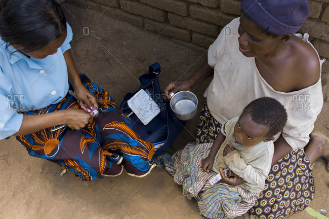 Thyolo, Malawi - April 22, 2013: A mother holds her sick child as community health monitor, Faines Labana prepares some antibiotics as she makes her rounds to remote villages checking on residents in the Ndallam Village