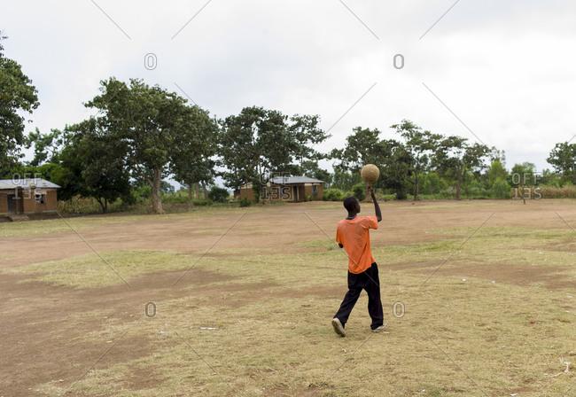 A kid walks through a soccer field in Luchenza, Malawi