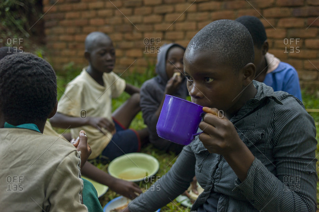 Thyolo, Malawi - April 25, 2013: A girl shares a meal with other orphaned children