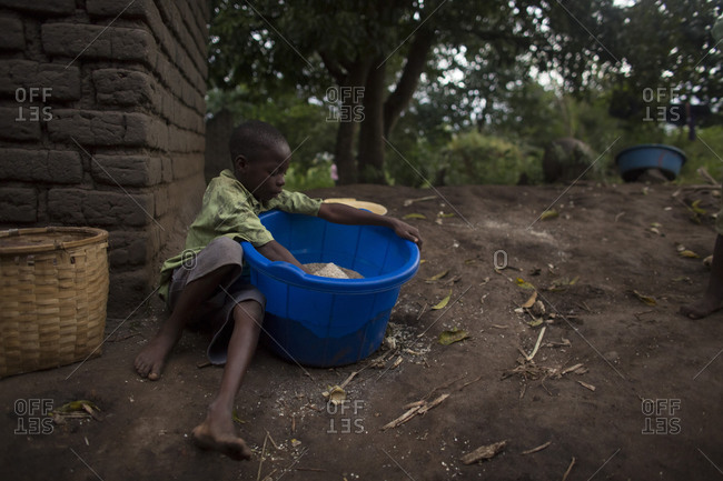 Luchenza, Malawi - April 26, 2013: A child orphaned by AIDS prepares food