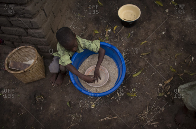 Luchenza, Malawi - April 26, 2013: A child orphaned by AIDS prepares rice