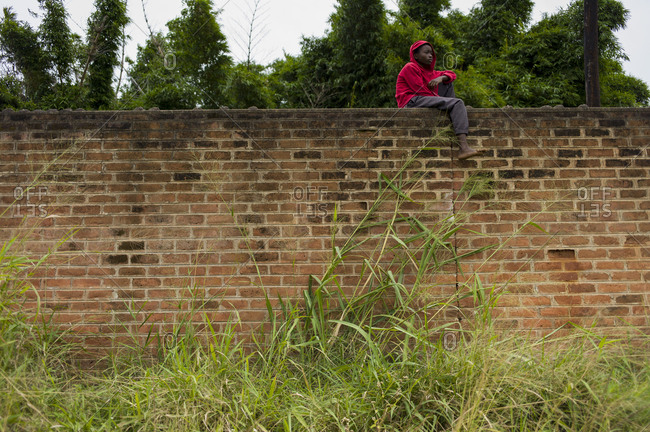 Luchenza, Malawi - April 27, 2013: Kid sitting on brick wall before free benefit show put on by Komai and Fochta featuring LA band Islands and Malawi's very own Ben Michaels