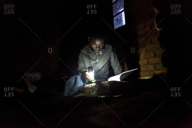 Thyolo, Malawi - April 29, 2013: A young boy orphaned by AIDS reads with a flashlight