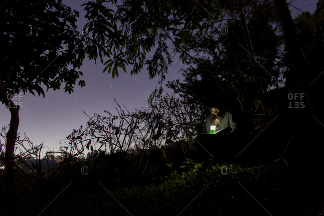 Thyolo, Malawi - April 29, 2013: A young boy orphaned by AIDS reads outside with a flashlight