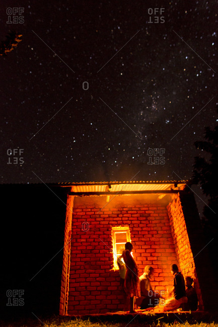 Thyolo, Malawi - April 29, 2013: Orphaned children sit outside at night