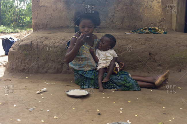 Ndallam Village, Malawi - April 30, 2013: Lekeleni Harrison feeds her daughter Abigirl (1 year 4 months) who is unable to walk and is being checked for polio