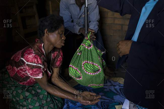 Ndallam Village, Malawi - April 30, 2013: Patrick Pedro who was born less then 7 days ago from parents who are both HIV positive receives a visit from Faines Labana a community health monitor