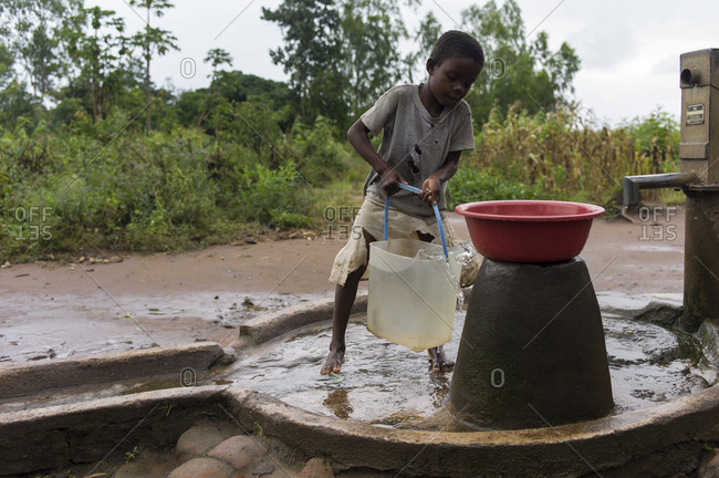 Thyolo, Malawi - May 2, 2013: A child pumps water in a small village