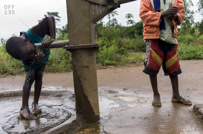 Thyolo, Malawi - May 2, 2013: A child drinks water from a well