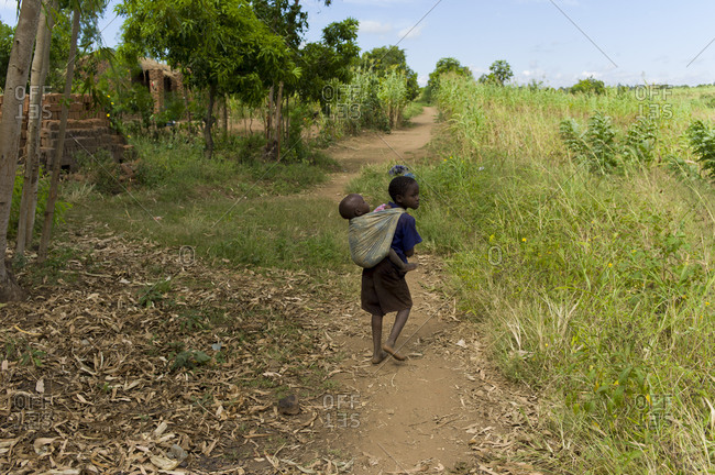 Luchenza, Malawi - April 21, 2013: A small child carries a baby on her back