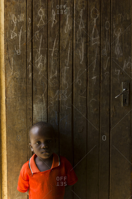 Luchenza, Malawi - April 21, 2013: A little boy stands in front of a door