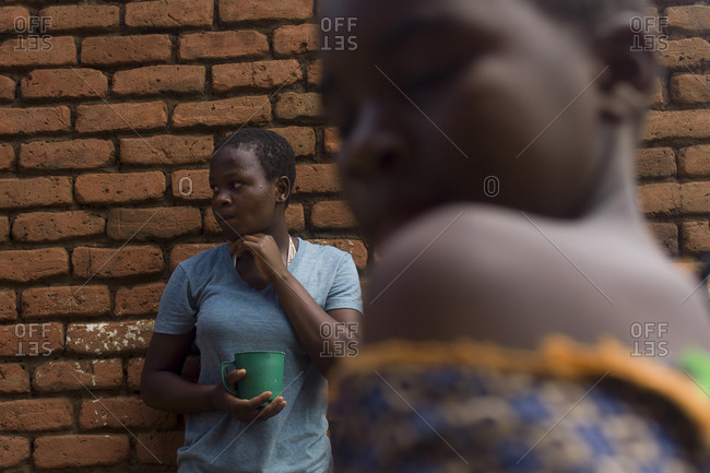 Luchenza, Malawi - April 21, 2013: Two teenagers stand by a wall