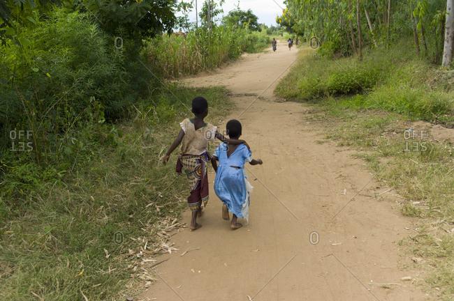 Two girls walk down a path in Luchenza, Malawi