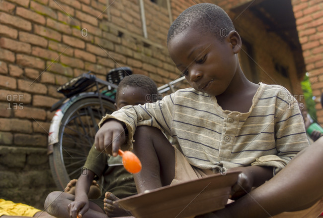 Luchenza, Malawi - April 21, 2013: Two boys eating outside of a building