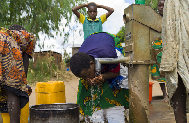 Luchenza, Malawi - April 21, 2013: A woman drinks from a well