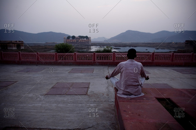 A man prays near the water palace, in Jaipur City, India