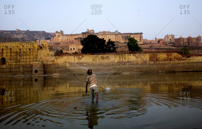 A man fishes with a net in a lake just outside Jaipur City, India