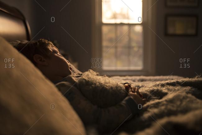 Young boy asleep in bed asleep in sunlight