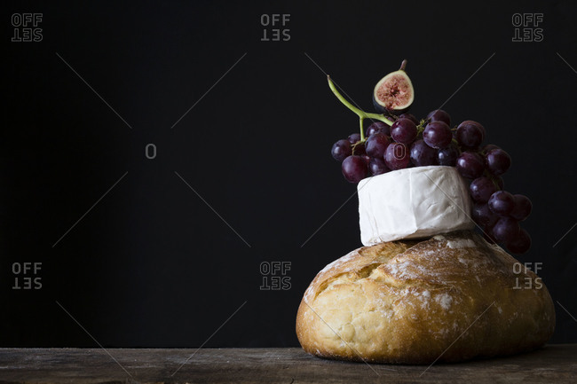 Loaf of bread and cheese with ripe fruits