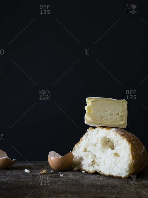 Piece of bread and cheese with an eggshell on a tabletop