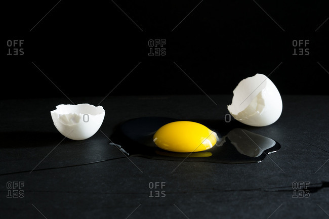 Close up of an egg cracked open on black surface