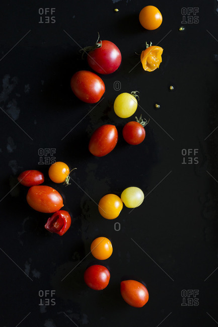 A variety of cherry tomatoes on black background