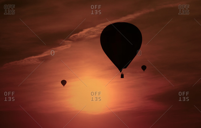 Silhouettes of three air balloons in front of red evening sky