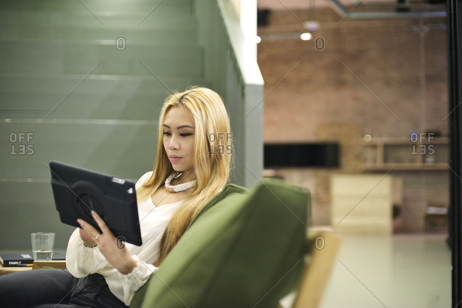 Woman using a tablet computer in a lobby