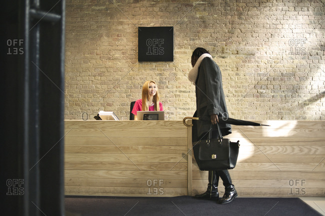Young receptionist greeting a guest