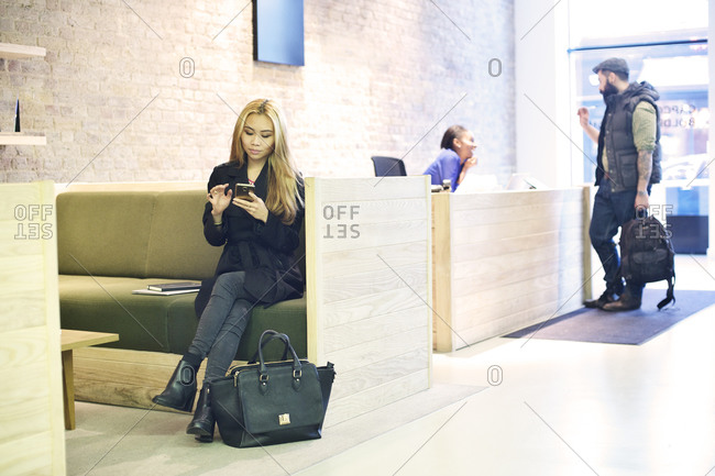 Woman checking mobile phone in lobby