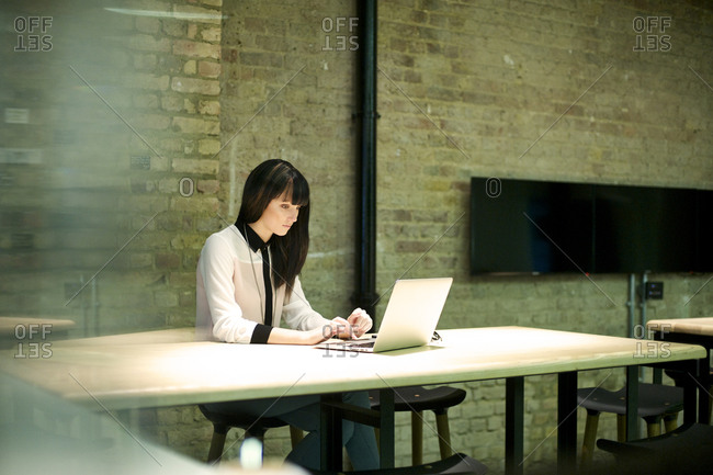Young businesswoman typing on laptop
