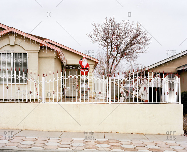 Santa Claus and Christmas lights outside of a house
