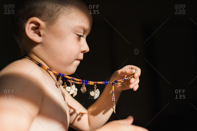 Young boy holding a necklace