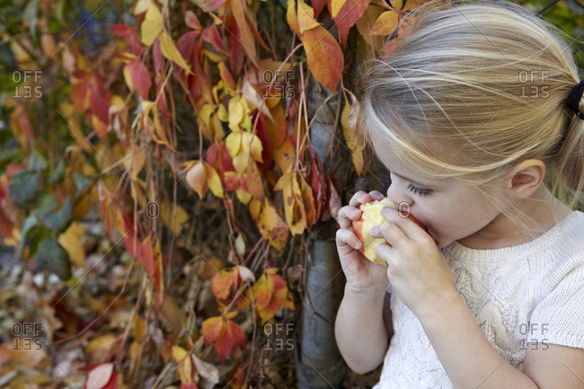 Young girl biting into an apple.