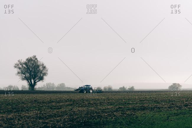 Tractor plowing a field in Osterlen, Sweden