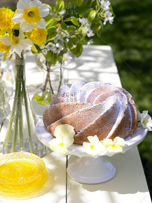 A cake surrounded by flowers on an outdoor table