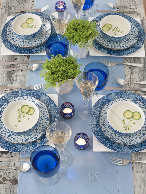 Creamy cucumber soup served on a blue and white table setting
