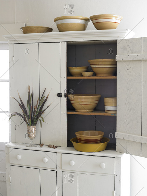 A white hutch filled with pottery