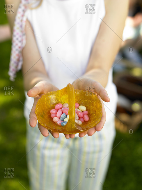 A girl holds a candy basket filled with jelly beans